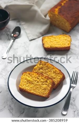 Slices of orange sponge cake and caramel sauce on marble background #385208959