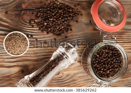 Black pepper on a wooden table #385629262