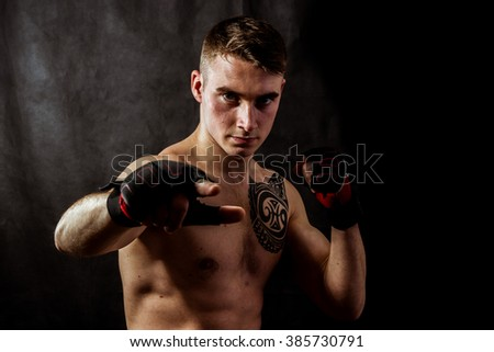 Angry fighter in  gloves Black background #385730791
