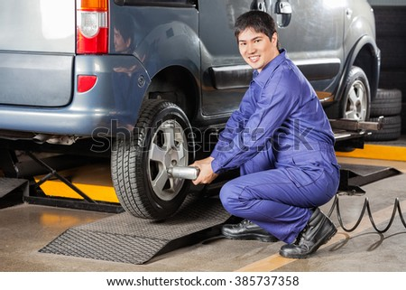 Happy Mechanic Fixing Car Tire At Repair Shop #385737358