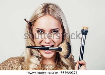 Closeup portrait of woman with makeup brush near face Royalty-Free Stock Photo #385920391
