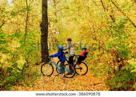 Family on bikes in autumn park, father and kids cycling, active family sport outdoors  #386090878