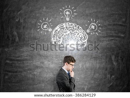 Brain and three bulbs drawn on black chalkboard. Man with hand in chin in front. Concept of mental activity.