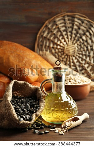 Composition of sunflower seeds, bread and oil on wooden table background, closeup #386444377