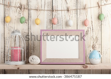 Easter decoration with blank wooden frame on the shelf