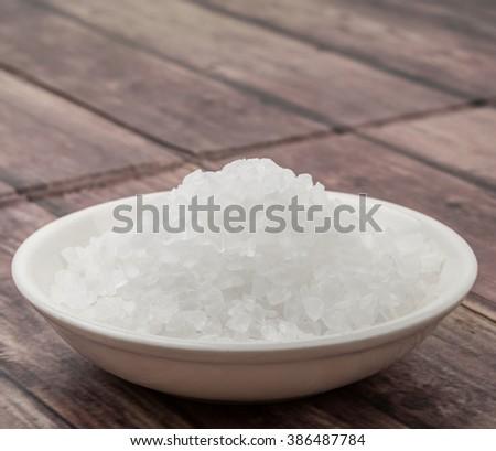 Sea salt in wooden bowl over wooden background #386487784