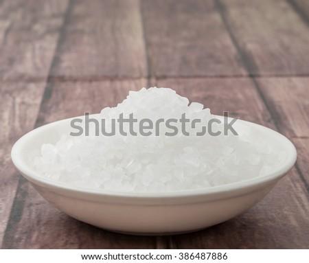 Sea salt in wooden bowl over wooden background #386487886