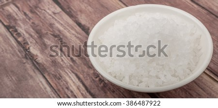 Sea salt in wooden bowl over wooden background #386487922