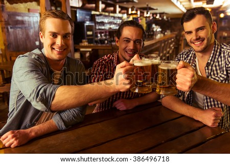 Three young men in casual clothes are smiling, looking at camera and clanging glasses of beer together while sitting in pub #386496718