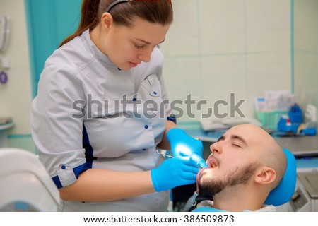 cute young boy checks his teeth in a dental office at the doctor. Medicine, dentist, health and stomatology concept #386509873