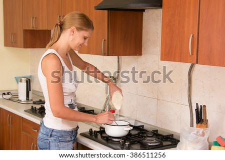 Young girl housewife prepares porridge in the kitchen #386511256