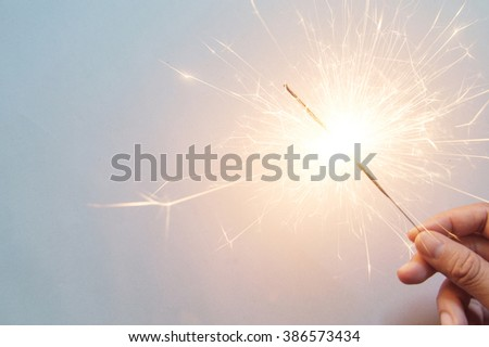 man's hand holding a sparkler on the white background #386573434