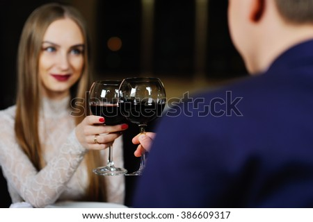 a man with a woman drinking red wine in a restaurant #386609317