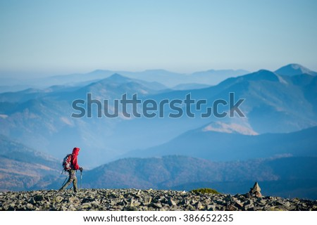 Tourist is walking on the rocky mountain on backpacking trip. Man is wearing red jacket and backpack on. Beautiful mountains on background. Eco tourism and healthy lifestyle concept. Copy space. #386652235