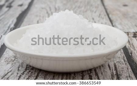 Sea salt in wooden bowl over wooden background #386653549