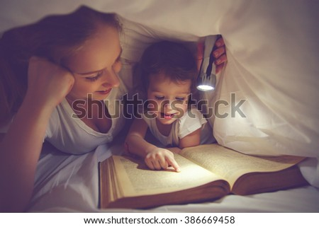 Family bedtime. Mom and child daughter reading a book with a flashlight under the blanket in bed #386669458