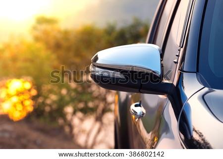 Black car side mirror with sun light effect.  #386802142