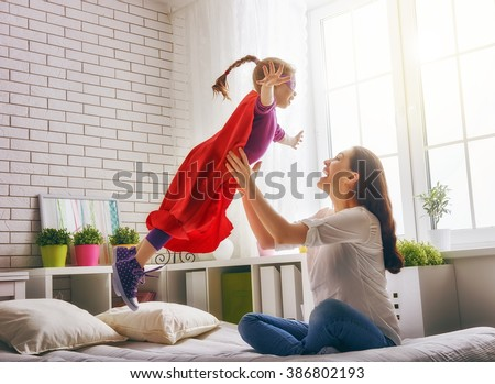 Mother and her child girl playing together. Girl in an Superman's costume. The child having fun and jumping on the bed.