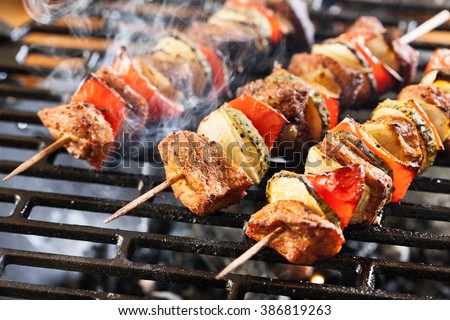 Grilling shashlik on barbecue grill. Selective focus #386819263