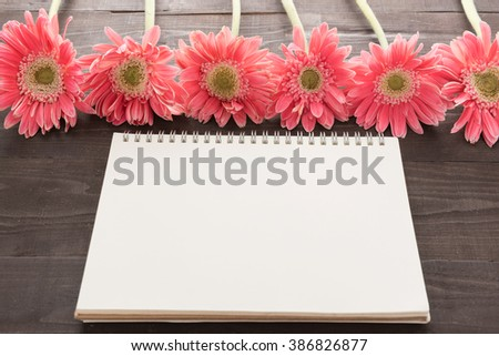 Pink gerbera flowers and notebook are on the wooden background.