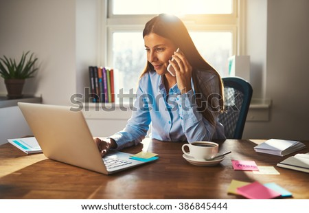Woman working on laptop at office while talking on phone, backlit warm light Royalty-Free Stock Photo #386845444
