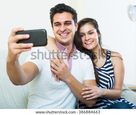 Happy young couple hugging and doing selfie in domestic interior #386884663