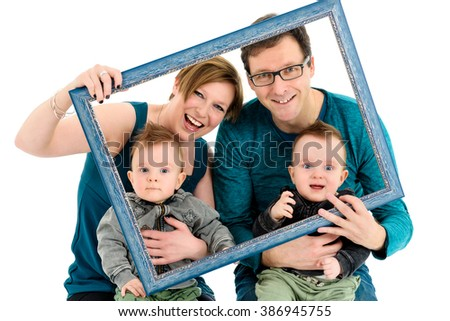 Happy family with identical twins is laughing.  They are holding a picture frame to make a creative effect on family portrait. Isolated on white.