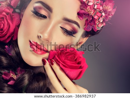Spring model with flowers in her hair and fashion makeup . Summer girl with trendy make up and hairstyle . #386982937
