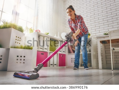 Beautiful young woman makes cleaning the house. Woman vacuums the floor #386990176