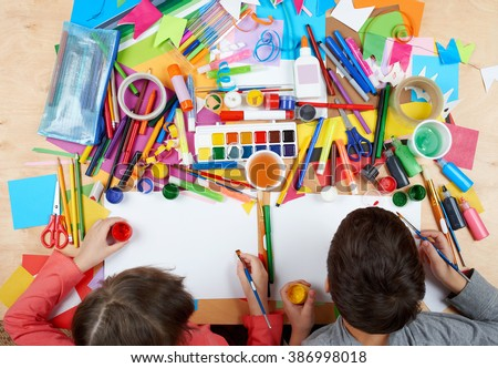 Child drawing top view. Artwork workplace with creative accessories. Flat lay art tools for painting. #386998018