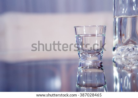 A vodka glass with a bottle standing on the glass table / vodka glass #387028465