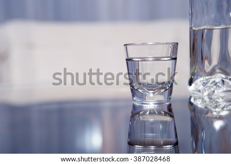 A vodka glass with a bottle standing on the glass table / vodka glass #387028468