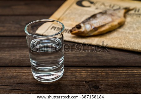 Shot of vodka with a stockfish and newspaper on an old wooden table. Close up view, focus on the shot of vodka #387158164