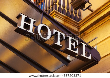 A luxury hotel entrance with sign.