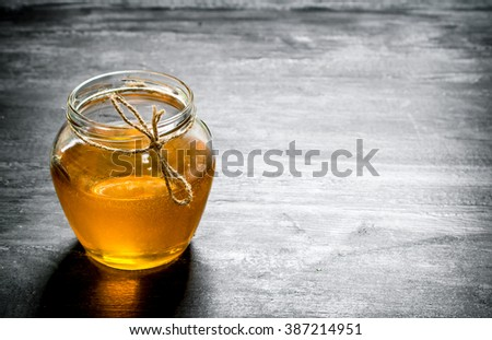 jar of natural honey . On the black rustic table. #387214951
