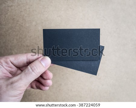 Closeup of hand holding two black business cards, Mockup