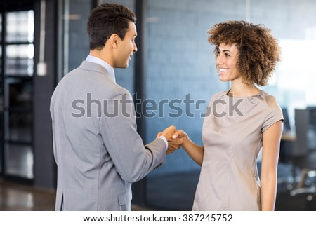 Businessman shaking hands young woman in office #387245752