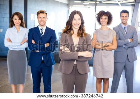 Portrait of confident business team standing in office with their hands crossed #387246742