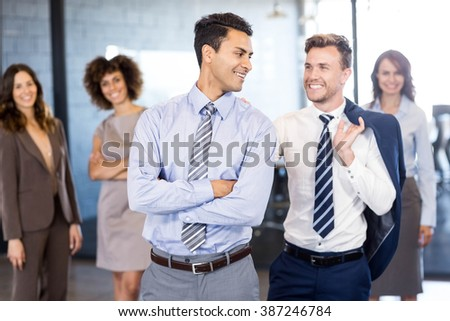 Smiling businessmen standing in front while businesswomen standing behind them in office #387246784