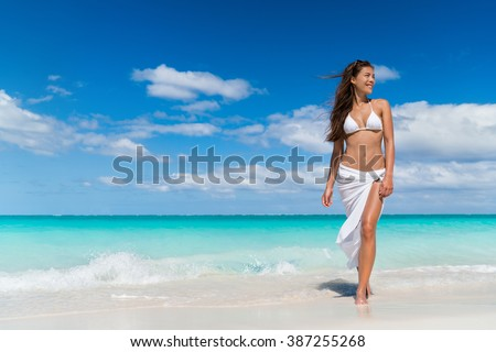 Beach woman in fashion beachwear white cover-up skirt clothing. Asian girl tourist wearing white pareo for sun protection relaxing walking in ocean water on summer vacation travel. #387255268