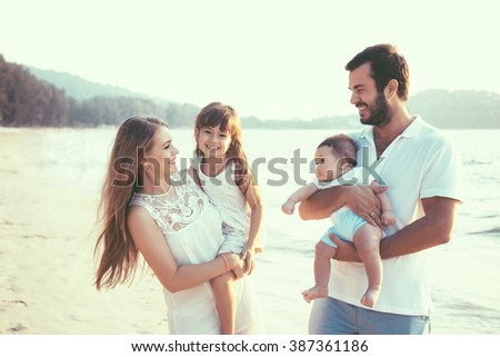 Family walking on the evening beach during sunset. Children with parents. #387361186