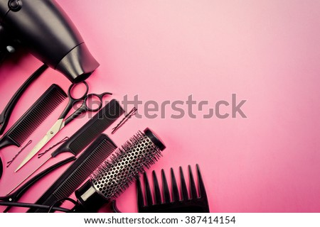 Hairdresser set with various accessories on pink background Royalty-Free Stock Photo #387414154