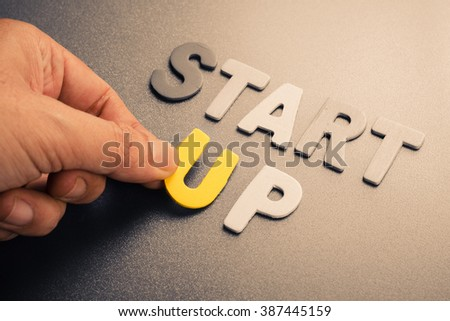 Hand arrange wood letters as Start-Up text #387445159