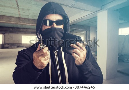 Threatening situation concept. Masked criminal holding a knife and loots. Selective focus image cross processed for dramatic look #387446245