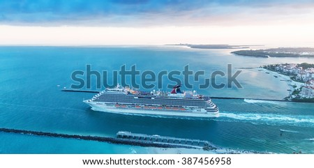 MIAMI - FEBRUARY 27, 2016: Aerial view of Cruise Ship departing from Miami Port. The city is a famous tropical destination for cruises. #387456958
