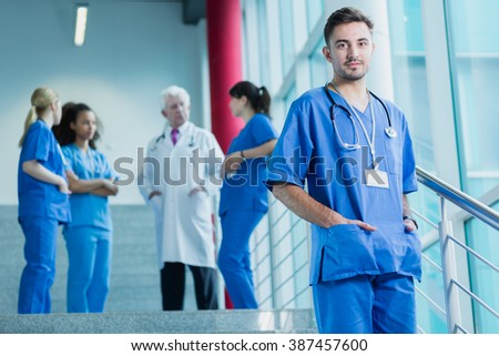 Student of medicine in blue uniform with stethoscope, in the background doctor standing with group of students #387457600