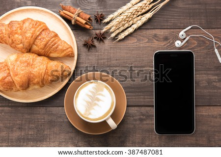 Coffee cup and fresh baked croissants, earphones, smart phone on wooden background. Top View. #387487081