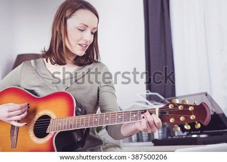 Happy brown haired smiling girl playing some records on guitar #387500206