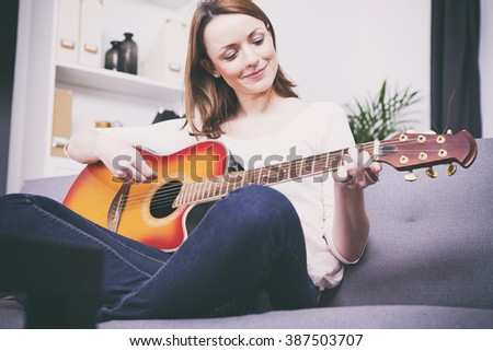 Pretty young girl having her legs crossed playing some record on guitar sitting on couch #387503707