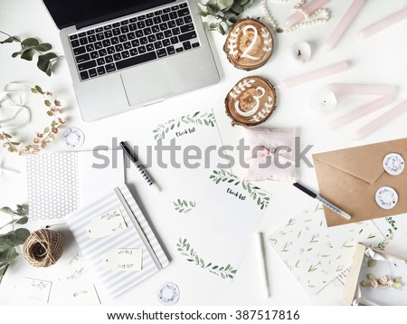 Workspace. Workspace with laptop, handmade invitation lists, craft envelope, pen, twine, candles and watercolor paintings on white background. Overhead view. Flat lay, top view